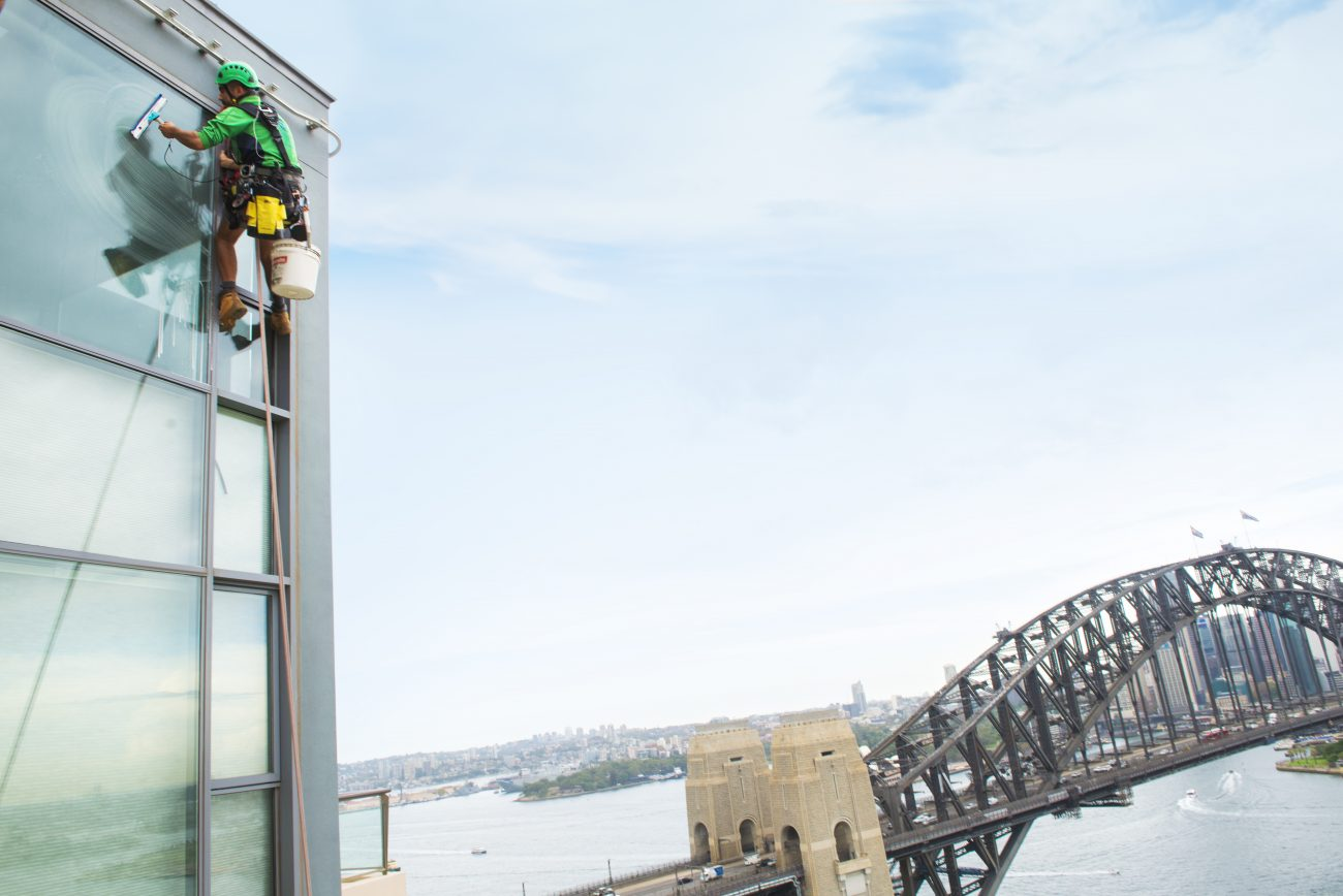 Man In Rope Cleaning The Glass Window - Commercial High Rise Window Cleaning - Magellan Company
