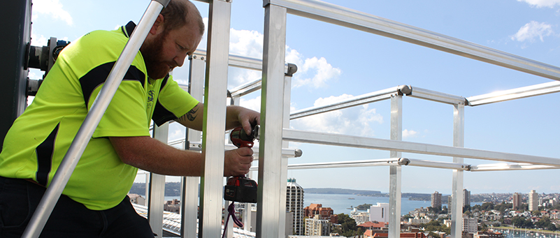Man Using Drilling Tool - High Rise Building Window Replacement - Magellan Company
